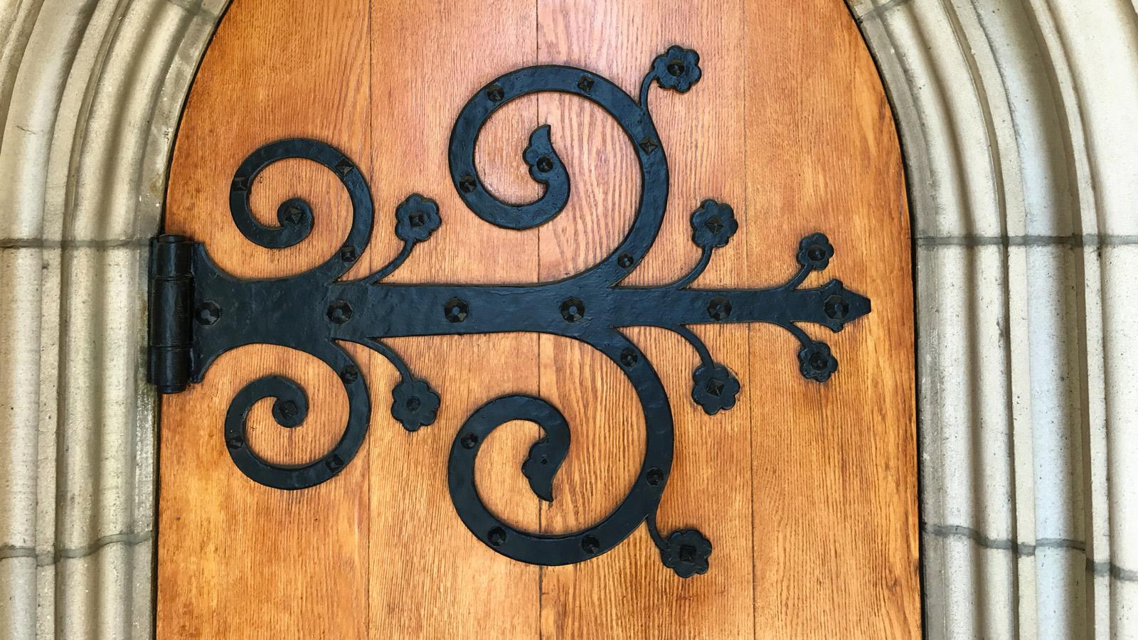 Image of scrolled iron door hinge on wooden door.