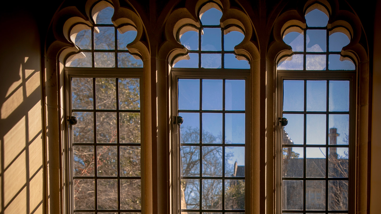 Image of gothic windows with sun shining in.