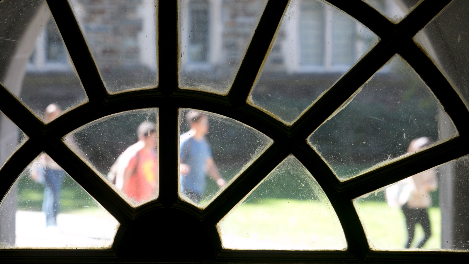 Image of blurry students walking outside as seen through an antique window.